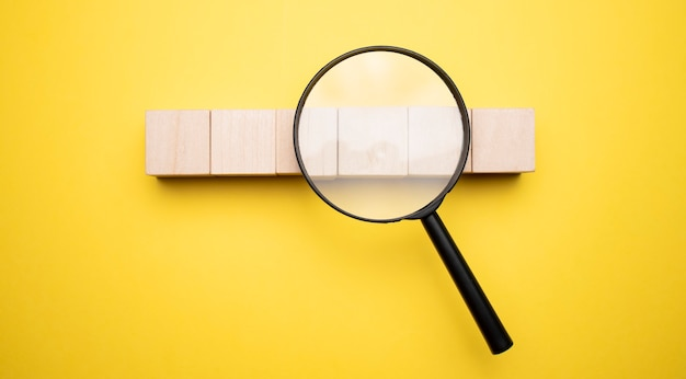 Cropped view of woman holding magnifying glass under wooden cubes with logo on yellow background