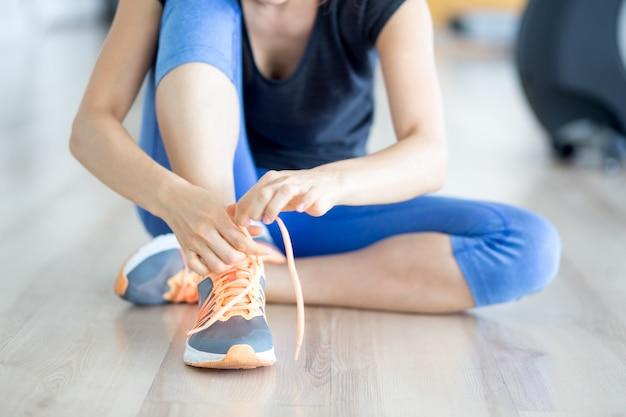 Vista ritagliata della donna che lega il pattino sul pavimento di ginnastica
