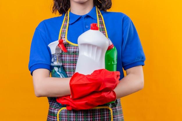 Vista ritagliata della donna che indossa un grembiule e guanti di gomma che tengono lo spazio dei prodotti per la pulizia