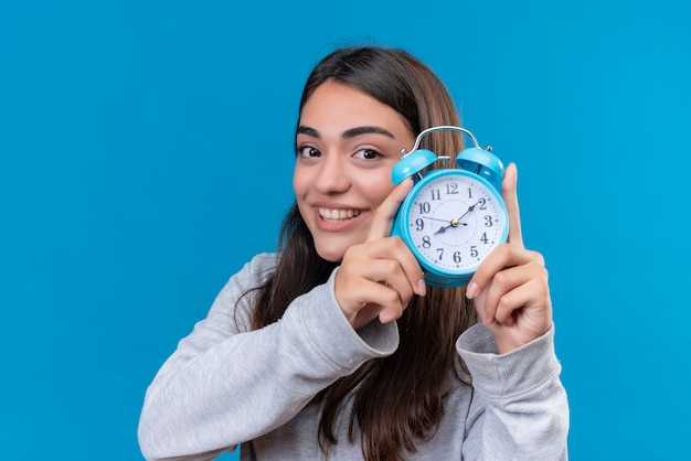 Cropped view of young beautiful girl in gray holding clock  with smile on face standing over blue space