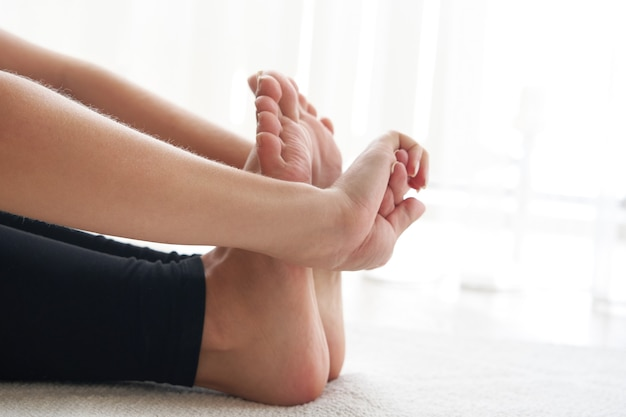 Cropped view of young woman practicing yoga sitting in seated forward bend exercise