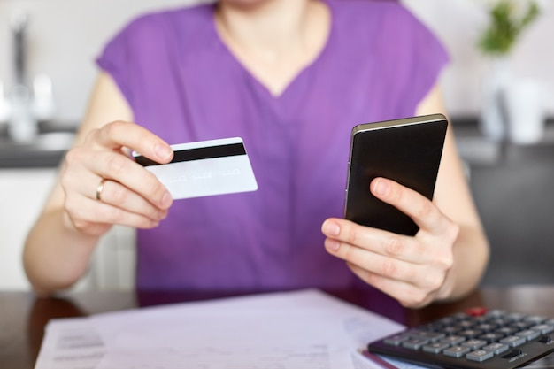 Cropped view of young woman in purple clothes sits at table, surrounded with documents, calculator, holds smart phone and plastic card, checks her bank account online, works at home. payment concept