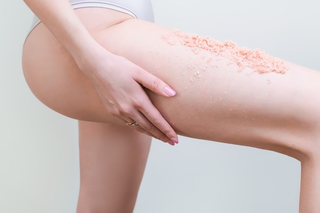 Cropped view of young woman with scrub applying scrub to legs.