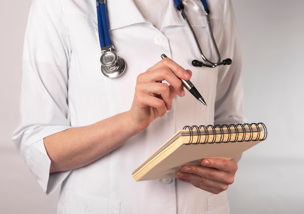 Cropped woman in medical uniform pointing with pen at notebook.