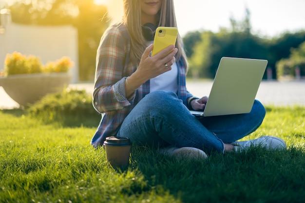 Обрезанная женщина текстовых сообщений смартфона, сидя на траве снаружи в парке счастливая и улыбающаяся девушка работает