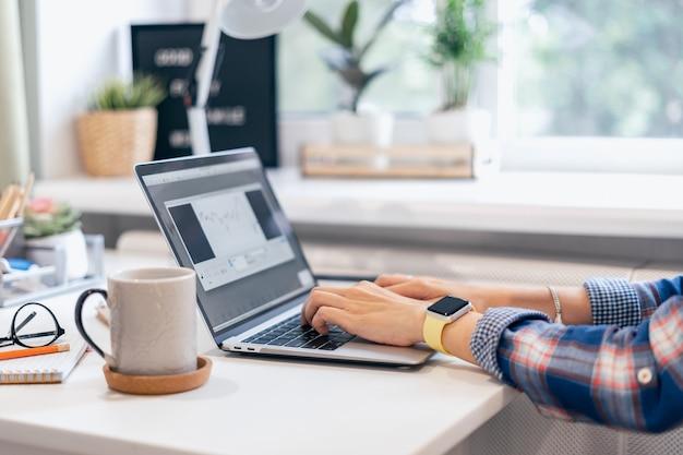 집에 앉아있는 동안 랩톱 컴퓨터에 입력하는 자른 여자. 커피 컵과 인간의 손을 닫습니다
