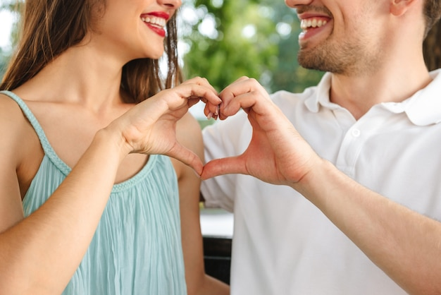 Cropped young cute loving couple sitting outdoors while showing heart love gesture