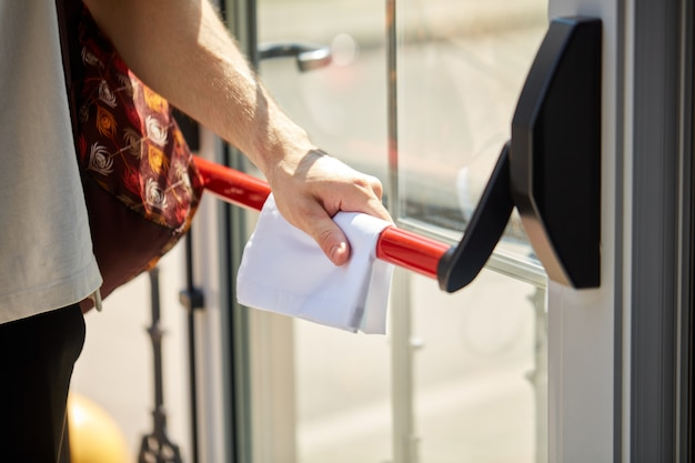 Обрезанный молодой мужчина пытается открыть дверь, используя защитную тряпку