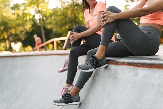 콘크리트 운동장에 앉아서 이야기하는 운동복에 잘린 젊은 슬림 여성