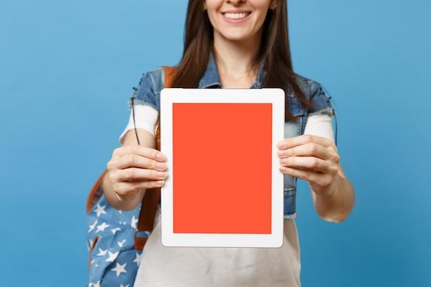 파란색 배경에 격리된 빈 검은색 빈 화면이 있는 태블릿 pc 컴퓨터를 들고 배낭을 메고 웃고 있는 젊은 갈색 머리 여자 학생. 대학에서 교육입니다. 광고 공간을 복사합니다.
