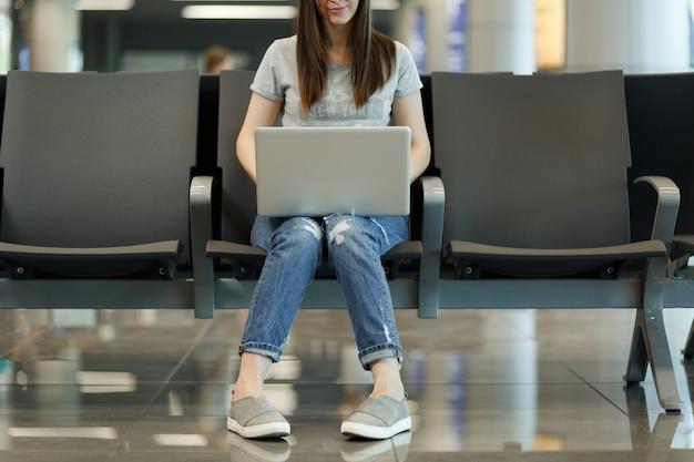 Ritagliata giovane turista sorridente donna turistica che lavora al computer portatile mentre aspetta nella hall dell'aeroporto internazionale