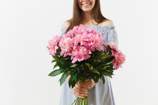 흰색 배경에 격리된 아름다운 분홍색 모란 꽃 꽃다발을 들고 파란 드레스를 입은 젊은 부드러운 여성. 성 발렌타인 데이 국제 여성의 날 휴일 컨셉입니다. 광고 영역