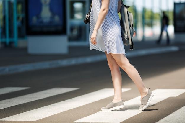 Обрезанный молодой путешественник турист женщина в легкой одежде с рюкзаком, стоя на пешеходном переходе в международном аэропорту