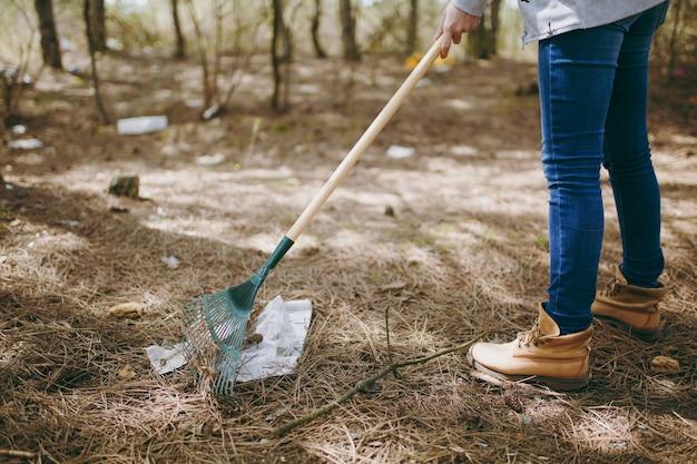흩어져 있는 공원에서 쓰레기 수거를 위해 갈퀴를 사용하여 쓰레기를 청소하는 캐주얼 옷을 입은 젊은 여성. 환경오염 문제