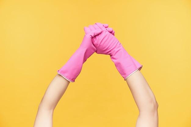 オレンジ色の背景で隔離の石鹸で手を洗っている間、ピンクの手袋でトリミングされた若い女性の手を交差させます。人間の手とクリーニングの概念