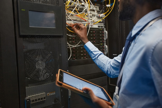 Cropper portrait of african american network engineer connecting cables in server cabinet while working with supercomputer in data center, copy space