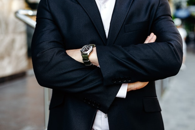 Cropping image folded male hands, one hand with watch closeup.