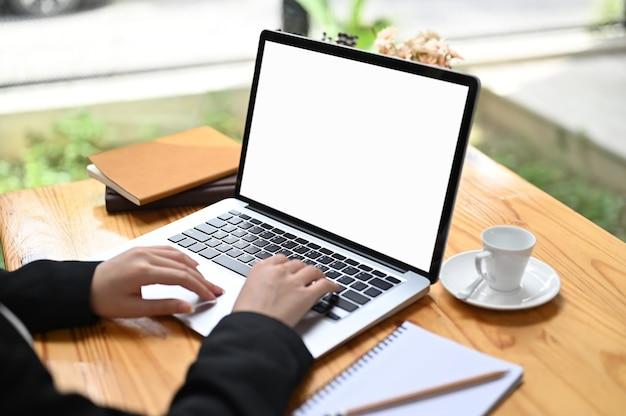 Обрезанный снимок bussinesswoman с помощью ноутбука с белым экраном на деревянном столе.