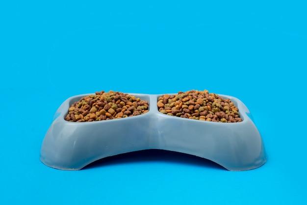Croquetas para perro servidas en un plato de color azul