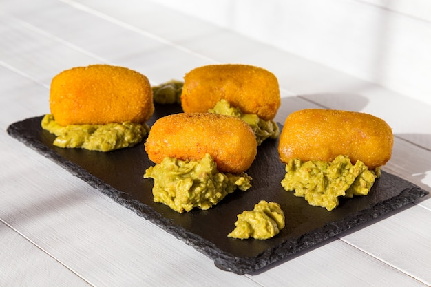 Крокеты, обжаренные в масле с соусом гуакамоле на черной каменной тарелке на кухне. вид сбоку