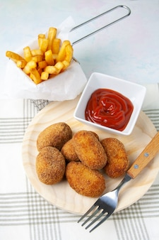 Croquettes on a wooden dish and chips