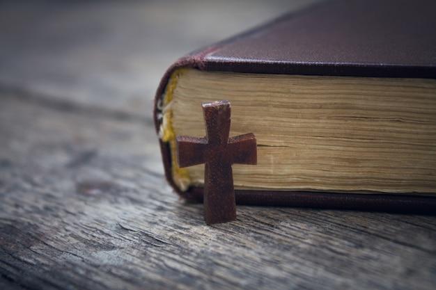 木の背景に十字架と聖書。