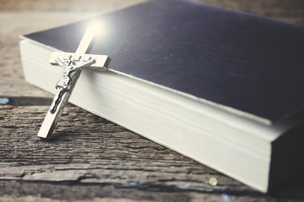 十字架と木製の背景の本