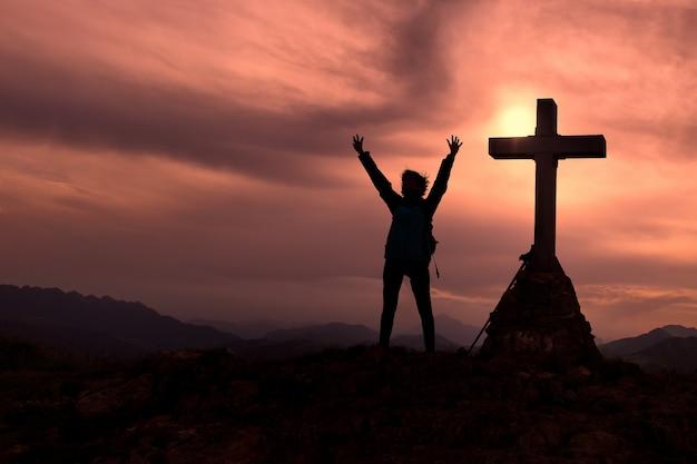 Крест на вершине горы с альпинистом, который поднимает руки