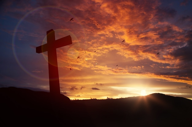 Cross on blurry sunset background,