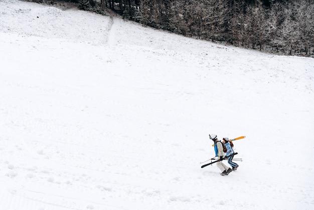 美しい冬の風景の中のクロスカントリースケート。 2人のスキーヤーが丘を歩いています。山でのスキーツーリング。曇り空。スポーツコンセプト
