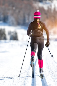 Cross-country skiing of a young athlete girl. classical alternating technique