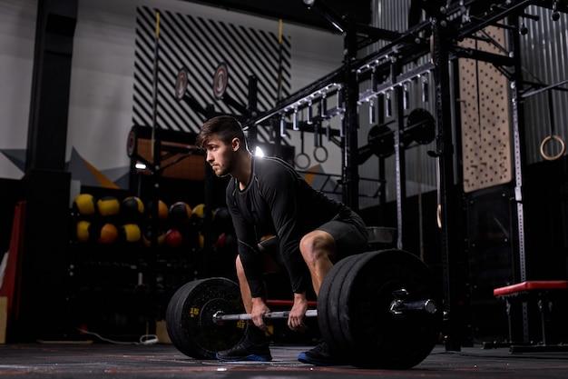 ジムでバーベルを持ち上げるクロスフィットアスリート。スポーツウェアで、ファンクショナルトレーニングパワーリフティングトレーニングエクササイズを一人で練習している男性。重量挙げ、ボディービルの概念