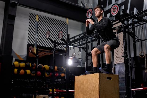 ジムでボックスジャンプ運動をしているクロスフィットアスリート男性。スポーツウェアで、ボックスにジャンプする若いフィットネス男。コピースペース。
