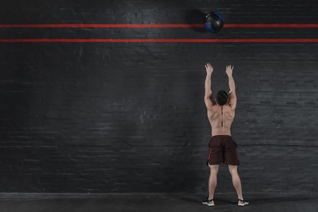 クロスフィットアスリートがジムでボールを投げます。ファンクショナルトレーニングをしているハンサムな男。トレーニング演習。レンガの壁のコピースペース。テキストの場所。