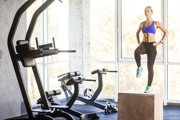 Женщина концепции кросс-пригонки в тренажерном зале шагает вверх на коробке