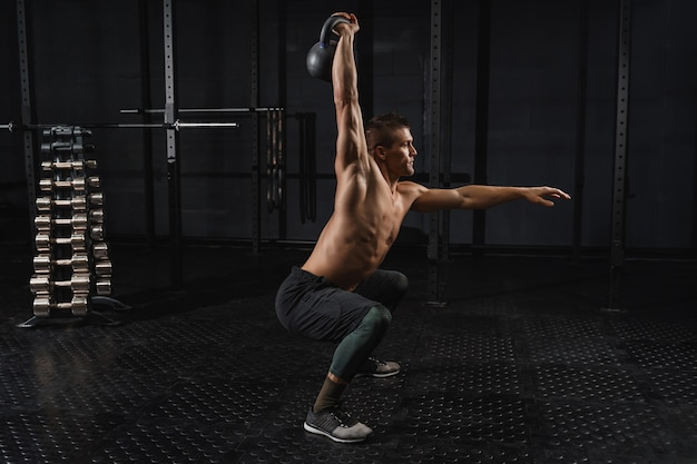 ジムでのクロスフィットトレーニング。ケトルベルはジムでエクササイズマンのトレーニングをスイングします。