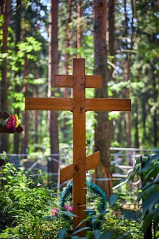 Cross on the grave, burial in the cemetery. wooden cross in the sun light
