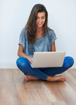 彼女のラップトップを使用して足を組んだ女の子