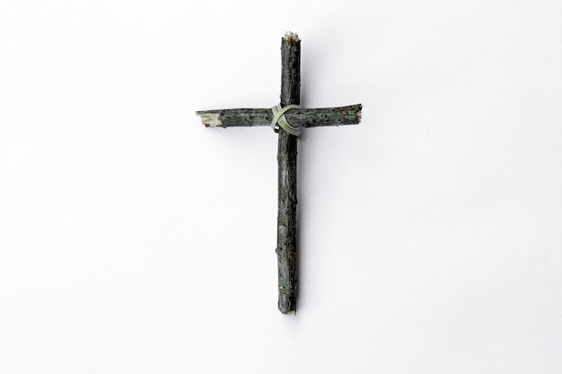 Cross made from tree branch isolated on white background