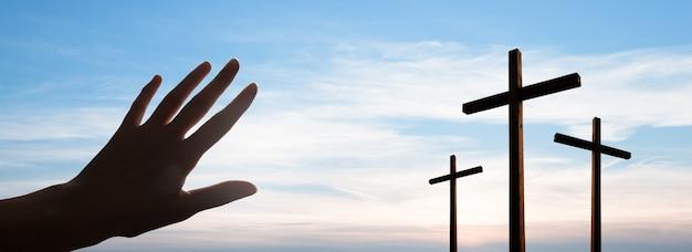 雲と劇的な日の出の空のパノラマの上に空のイエス・キリストの十字架。