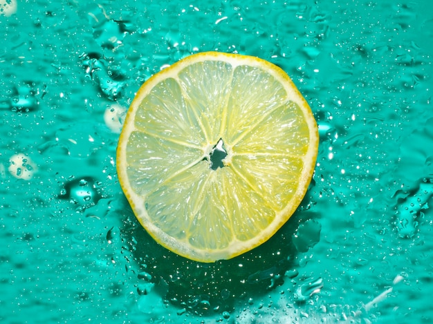 Cross-section of the juicy lemon on blue background
