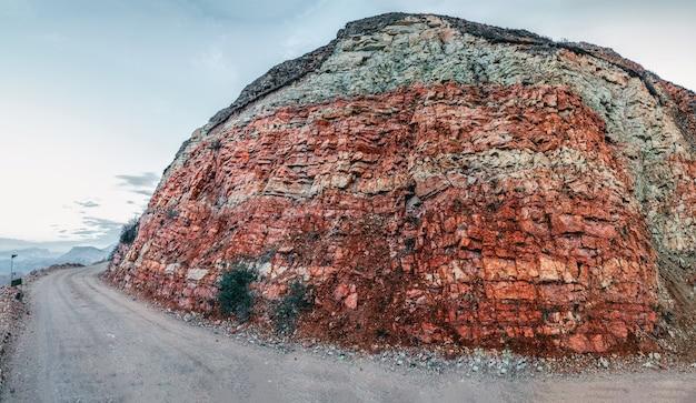바위의 단면입니다. 지질층. 산의 섹션에 있는 색색의 돌 층, 다른 암석층 및 토양 층.