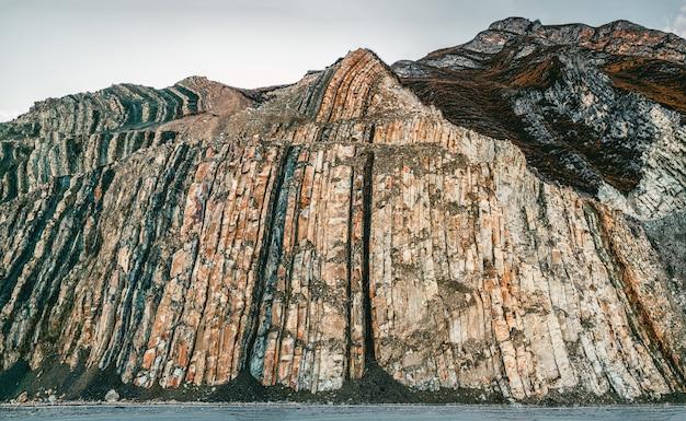 岩の断面。地層。マウントのセクションにある色付きの石の層、さまざまな岩層、土壌層。