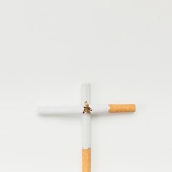 Cross sign made from broken cigarette over white background