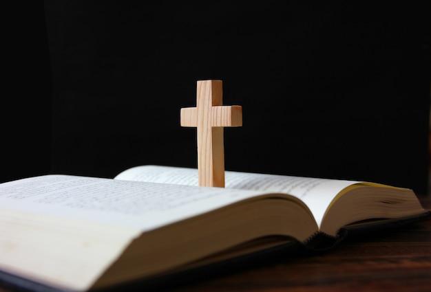 Крест стоя на книге изолировать на черном фоне