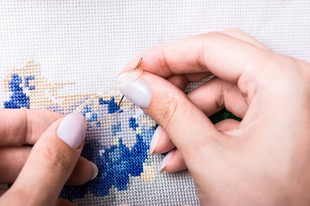 Cross-stitch on the canvas. the girl embroiders a thread and a needle