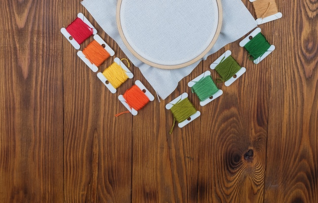 Cross stitch hoop with stretched canvas on wooden background with copyspace