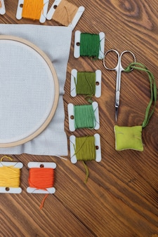 Cross stitch hoop with stretched canvas on wooden table with copyspace