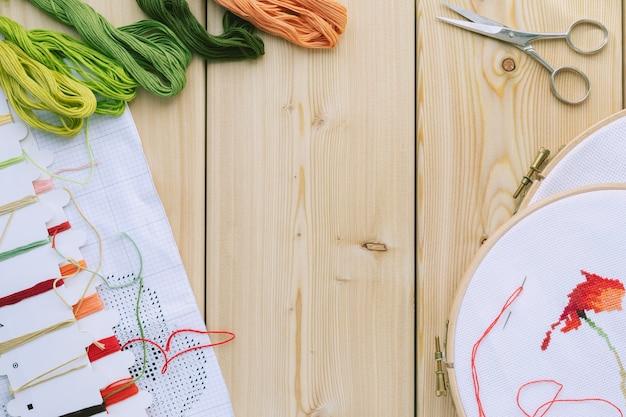 クロスステッチセット:刺繍された花柄のフープ、はさみ、キャンバス、カラフルな糸、カラーパレット、はさみ。木製のテーブル。趣味、手作りの家の装飾のコンセプト。 diy。コピースペース