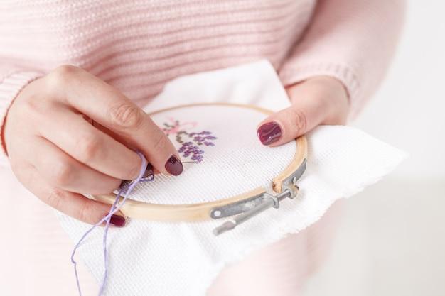 Вышитая крестиком подушка в женских руках